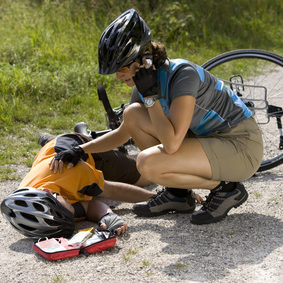 Germany, Bavaria, Oberland, Woman giving aid to fallen biker